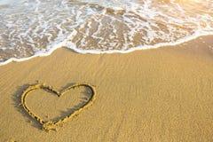 Hand dragen hjärta på strandsand över mjuk guld- solnedgång Förälskelse Arkivfoto