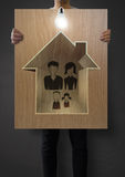 Hand draw family and house. Man show hand draw family and house on wooden poster as insurance concept stock photo