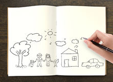 Hand draw in open book of lovely family. On wood table Royalty Free Stock Photos