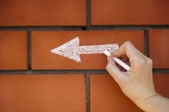 Hand drawing an arrow pointing left on the bricks Stock Photos
