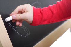 Hand drawing on blackboard. Child hand in red wear drawing on blackboard isolated Stock Photos