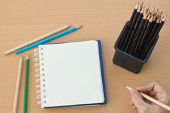 Hand drawing with blank paper on wooden. Hand drawing with blank paper and colorful pencils on wooden table Royalty Free Stock Image