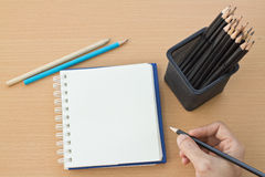 Hand drawing with blank paper on wooden. Hand drawing with blank paper and colorful pencils on wooden table Royalty Free Stock Photography