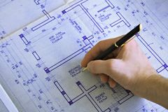 Hand drawing a blueprint. Right hand drawing a blueprint Stock Image