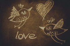 Hand drawing with chalk on blackboard, cute kawaii birds, heart and word love, St.Valentine´s Royalty Free Stock Image