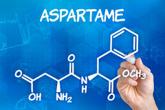 Hand drawing the chemical formula of aspartame. Hand with pen drawing the chemical formula of aspartame royalty free illustration