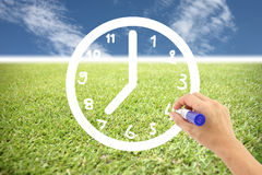Hand is drawing a clock on lawns and blue sky. Royalty Free Stock Photo