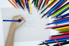 A hand is drawing with color pencils royalty free stock image