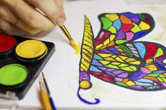 Hand drawing a colorful butterfly with a brush and glitter. Hand drawing a colorful butterfly with a brush and paints stock photo