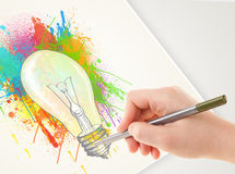 Hand drawing colorful idea light bulb with a pen. On paper Stock Photos