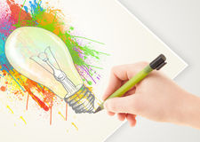 Hand drawing colorful idea light bulb with a pen. On paper Royalty Free Stock Photo