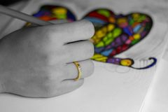 Hand drawing a colorful rainbow butterfly. Hand drawing a multicolored butterfly with a simple pencil of colors and glitter in black and white and color stock images