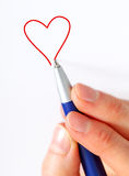 Hand drawing  a heart. A hand holding a blue pen and drawing a red heart Royalty Free Stock Images