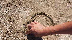 Hand drawing a heart on sand Stock Image