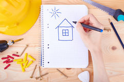 Hand drawing a house. And different tools  on a wooden background Royalty Free Stock Image