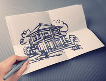 Hand drawing house on white folding paper background Stock Images