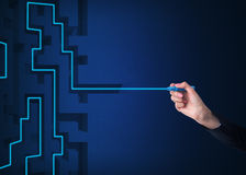 A hand is drawing a line as a maze solution. Dark blue background Royalty Free Stock Photography
