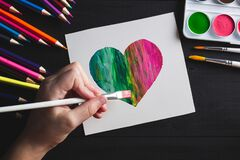 Hand drawing multi-colored heart with paints and pencils lying on black wooden table. Flat lay