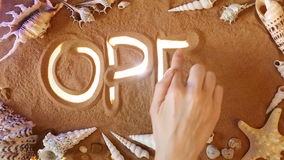 Hand drawing Open symbol in the sand. Beach background. Top view stock video footage