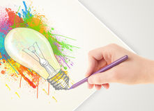 Hand drawing on paper a colorful splatter lightbulb Stock Photos