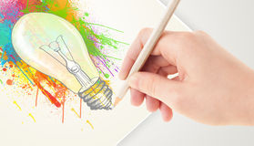 Hand drawing on paper a colorful splatter lightbulb Stock Images
