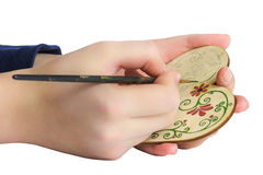 Hand drawing patterns on the wooden hearts. Woman paints a wooden heart Stock Photography