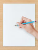 Hand drawing pencil on white paper with wood  background. Royalty Free Stock Photography
