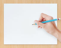 Hand drawing pencil on white paper with wood  background. Royalty Free Stock Photos