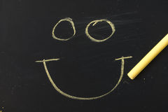 Hand drawing smiley face on blackboard Royalty Free Stock Images
