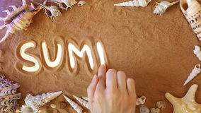 Hand drawing Summer symbol in the sand. Beach background. Top view stock video footage