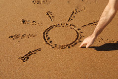 Hand drawing a sun in the sand. Naif sun being drawed in the sand on the beach Royalty Free Stock Image