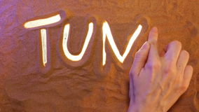 Hand drawing Tunis symbol in the sand. Beach background. Top view stock video