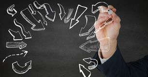 Hand drawing white arrow doodles against grey wall Stock Image