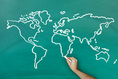 Hand drawing world map on blackboard. Hand holding chalk drawing world map on blackboard stock image