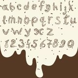 Lowercase English letters and numbers from pastry cream. Hand-drawn alphabet and numbers on the background of chocolate Royalty Free Stock Photos
