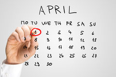 Hand drawn April calendar with the First ringed. Hand drawn calendar for April on a virtual interface or screen with the First ringed in red by a man holding a Stock Photography