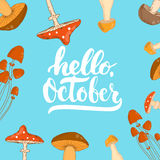Hand drawn Autumn typography lettering phrase Hello, October on the blue mushrooms background. Stock Photos