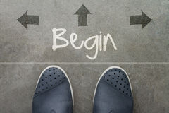 Hand drawn BEGIN design word on front of business man feet. As concept royalty free stock photo