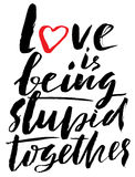 Hand drawn black lettering print. Love is being stupid together. St. Valentines Day. Royalty Free Stock Photo
