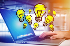 Hand drawn bulb lamp icon going out a computer interface of a ma. View of Hand drawn bulb lamp icon going out a computer interface of a man at the office - Idea Stock Image