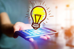 Hand drawn bulb lamp icon going out a smartphone interface of a. View of Hand drawn bulb lamp icon going out a smartphone interface of a man at the office Royalty Free Stock Photography