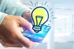 Hand drawn bulb lamp icon going out a smartphone interface of a. View of Hand drawn bulb lamp icon going out a smartphone interface of a man at the office Royalty Free Stock Photo
