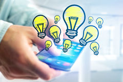 Hand drawn bulb lamp icon going out a smartphone interface of a. View of Hand drawn bulb lamp icon going out a smartphone interface of a man at the office Royalty Free Stock Image
