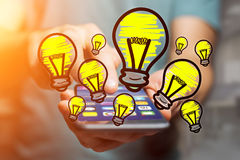 Hand drawn bulb lamp icon going out a smartphone interface of a. View of Hand drawn bulb lamp icon going out a smartphone interface of a man at the office Stock Image