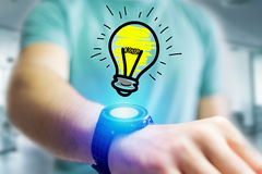Hand drawn bulb lamp icon going out a smartwatch interface of a. View of Hand drawn bulb lamp icon going out a smartwatch interface of a businessman at the Stock Photo