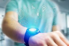 Hand drawn business icon going out a smartwatch interface of man. View of Hand drawn business icon going out a smartwatch interface of man at the office Stock Images