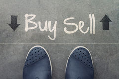 Hand drawn BUY or SELL design word on front. Of business man feet as concept royalty free stock photography