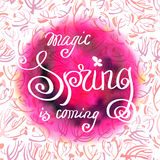 Hand drawn calligraphy card. Inspiration quote. Round watercolor background and quote magic spring is coming. Watercolor red pink blur blob design and floral Stock Illustration