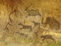 Hand-drawn cave drawings on sandstone wall. Ancient people, animals andpetroglyphs tribal travel traditional tourism symbol spear silhouette sheep prehistoric stock image
