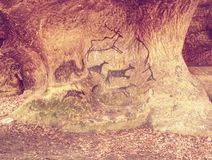 Hand-drawn cave drawings on sandstone wall royalty free stock photos
